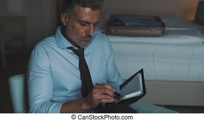 Mature businessman making notes in a hotel room. - Handsome...
