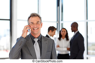 Mature businessman on phone in office