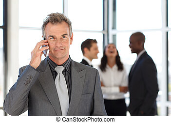 Mature businessman on phone with his team in the background