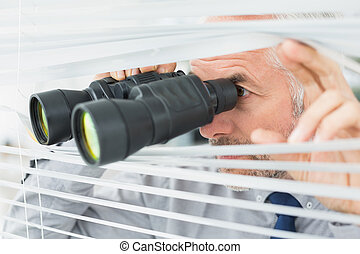 Mature businessman peeking with binoculars through blinds - ...