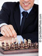 Mature businessman playing chess