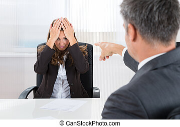 Businessman Pointing To Frustrated Businesswoman