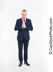 Mature businessman praying