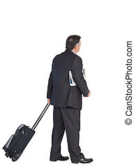 Mature businessman pulling his suitcase