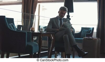 Mature businessman reading newspapers in a hotel lobby. Slow...