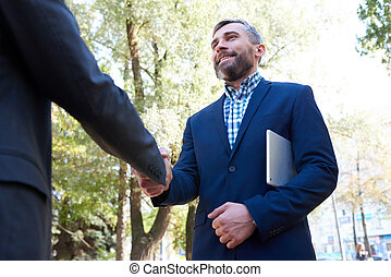 Mature Businessman Shaking Hands with Partner