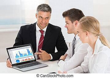 Mature Businessman Showing Graph To His Colleagues
