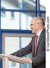 Mature Businessman Standing At Podium