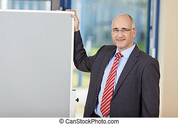 Mature Businessman Standing By Flipchart