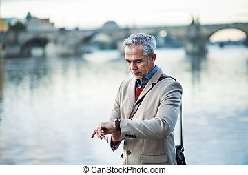 Mature businessman standing by river Vltava in Prague city, checking the time.