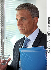 mature businessman standing close to the window