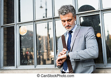 Mature businessman standing in a city. - Handsome mature...