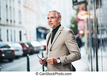 Mature businessman standing on a street in city, holding glasses.