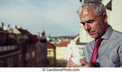 Mature businessman standing on a terrace in city, drinking...