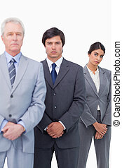 Mature businessman standing with his employees