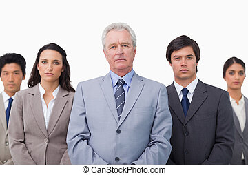 Mature businessman standing with his team