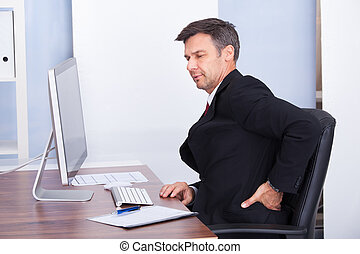 Mature Businessman Suffering From Back Pain While Working In Office