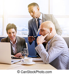 Mature businessman supervising his employees as they work