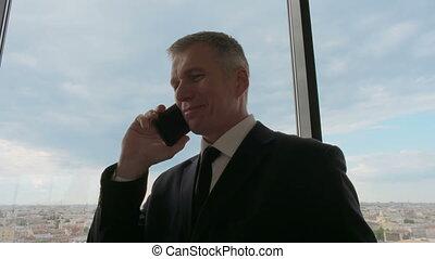 Mature businessman taling on phone