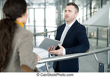 Mature Businessman Talking to Colleague in Hall