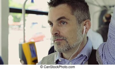 Mature businessman travelling by tram, listening music. -...