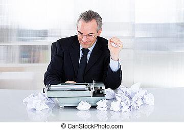 Mature businessman typing on typewriter