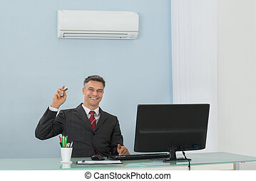 Mature Businessman Using Air Conditioner In Office