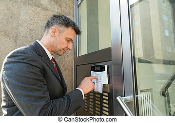 Businessman Using Door Security System On Wall