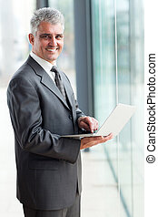 mature businessman using laptop computer
