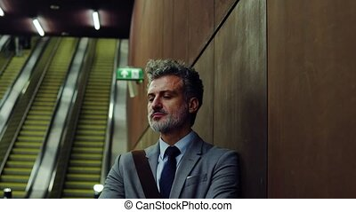 Mature businessman waiting on a metro station. - Handsome...