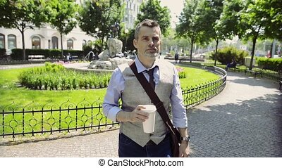 Mature businessman walking in the city park with cup of coffee.