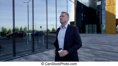 Mature businessman walking with coffee
