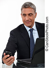 Mature businessman with a laptop and cellphone