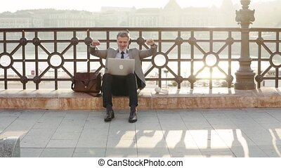 Mature businessman with a laptop in a city.