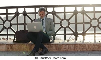 Mature businessman with a laptop in a city. - Handsome...