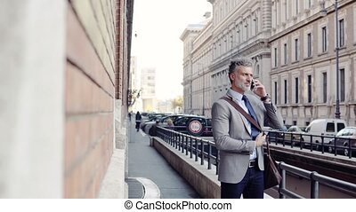 Mature businessman with a smartphone in a city.