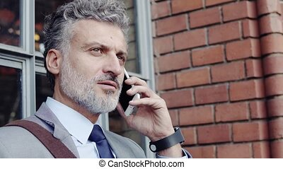 Mature businessman with a smartphone in a city. - Handsome...