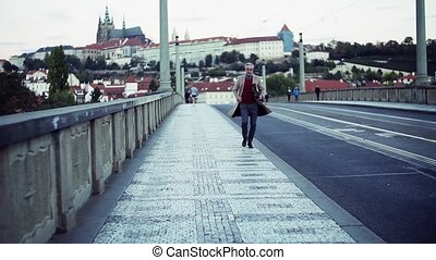 Mature businessman with bag running on a bridge in Prague...
