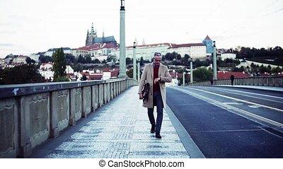 Mature businessman with bag walking on a bridge in Prague city.