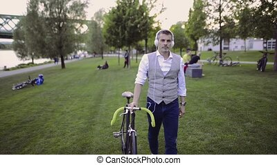 Mature businessman with bicycle and earphones in city park.