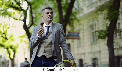Mature businessman with bicycle in the city eating ice...