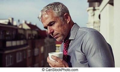 Mature businessman with coffee standing on a terrace in...