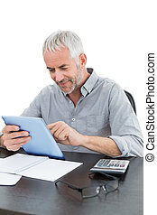 Mature businessman with digital tablet and calculator at desk
