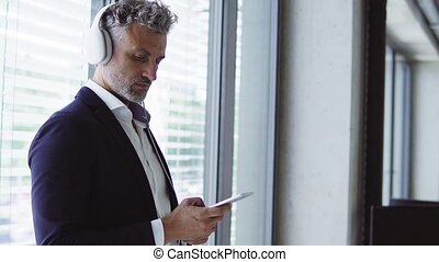 Mature businessman with earphones and smartphone.