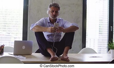 Mature businessman with earphones and smartphone. - Mature...