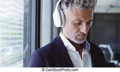 Mature businessman with earphones. - Mature businessman in...