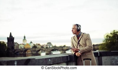 Mature businessman with headphones and smartphone standing...