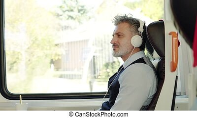 Mature businessman with headphones travelling by train. -...