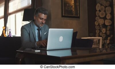Mature businessman with laptop in a hotel lobby. - Mature ...