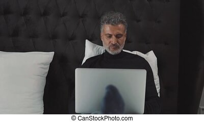 Mature businessman with laptop in a hotel room. Handsome man...